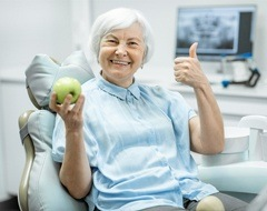 older woman holding apple thumb up
