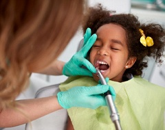 little girl getting her teeth cleaned by a hygienist