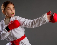 little girl wearing a mouthguard and a karate uniform
