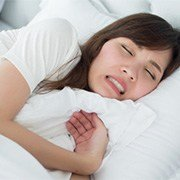 A woman sleeping and clenching her teeth.