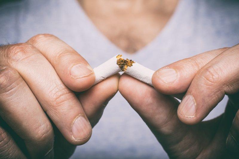 person breaking cigarette